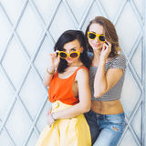 Beautiful young couple fashionable girls blonde and brunette in a bright yellow dress and sunglasses posing and smiling for the ca Royalty Free Stock Photo