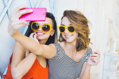 Beautiful young couple fashionable girls blonde and brunette in a bright yellow dress and sunglasses posing and smiling for the ca Stock Images