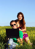Beautiful young couple in a field with a computer. Happy couple on a laptop computer outdoors. Lay on the green grass Stock Photo