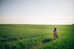 Beautiful young couple gently hugging in sunshine in spring green field. Happy family embracing in green meadow with fresh grass. In sunlight. Romantic moments stock photo