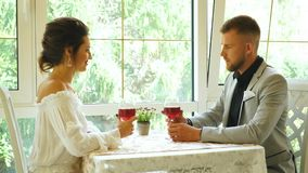 Beautiful young couple with glasses of red wine in luxury restaurant. Happy couple in restaurant looking each other and toasting stock video footage