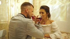 Beautiful young couple with glasses of red wine in luxury restaurant. Happy couple in restaurant looking each other and toasting stock footage