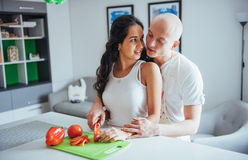 Beautiful young couple grinds vegetables together in the kitchen. stock photos