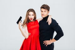 Beautiful young couple with gun standing and hugging Royalty Free Stock Photography