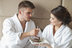 Beautiful young couple having breakfast in bed. Stock Photo
