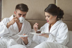 Beautiful young couple having breakfast in bed. Royalty Free Stock Photos