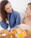 Beautiful young couple having breakfast in bed together Royalty Free Stock Photos