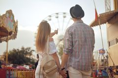 Beautiful, young couple having fun at an amusement park. Couple Dating Relaxation Love Theme Park Concept. Couple posing together. On the background of a ferris Stock Images