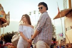 Beautiful, young couple having fun at an amusement park. Couple Dating Relaxation Love Theme Park Concept. Couple posing together. On the background of a ferris Royalty Free Stock Photo