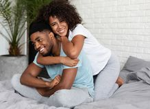 Beautiful young couple having fun in bedroom at home stock images