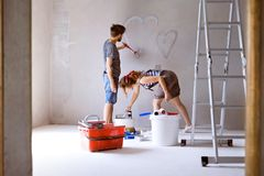 Couple painting hearts on the wall in their house. Royalty Free Stock Image