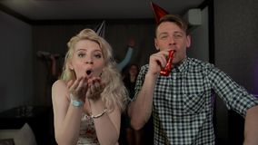 Beautiful young couple having fun at party blowing party whistles confetti stock video