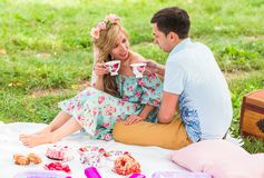 Beautiful Young Couple Having Picnic in Countryside. Happy Family Outdoor. Smiling Man and Woman relaxing in Park Stock Photography