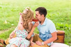 Beautiful Young Couple Having Picnic in Countryside. Happy Family Outdoor. Smiling Man and Woman relaxing in Park Royalty Free Stock Image