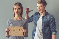 Beautiful young couple. Is having a quarrel. Girl is holding a cardboard tablet with word Sorry while her boyfriend is screaming on her, on gray background royalty free stock photo