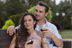 Beautiful young couple having red wine in park Royalty Free Stock Image