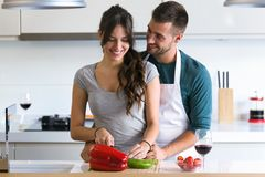 Beautiful young couple having romantic moments, hugging and cutting vegetables in the kitchen at home. stock photo