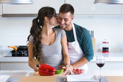 Beautiful young couple having romantic moments, hugging and kissing while cutting vegetables in the kitchen at home. stock photography