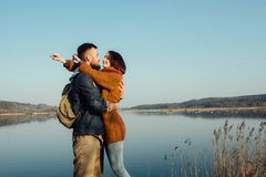 Travel and love. Happy young couple walking along the shore of blue lake in hipster clothes. Beautiful young couple in hipster clothes hugging in the background stock image