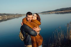 Travel and love. Happy young couple walking along the shore of blue lake in hipster clothes. Beautiful young couple in hipster clothes hugging in the background stock images