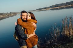 Travel and love. Happy young couple walking along the shore of blue lake in hipster clothes. Beautiful young couple in hipster clothes hugging in the background royalty free stock photos