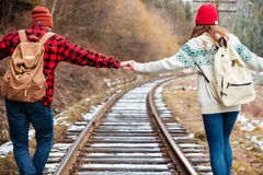 Beautiful young couple holding hands and walking along railroad together Stock Image
