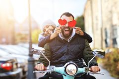 Beautiful young couple holding hearts while riding scooter in city in autumn stock photo