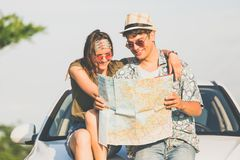 Beautiful young couple holding map outdoors. Road trip summer vacation concept. Young hipster couple sitting on car hood and looking at map. Travel on the road stock photography