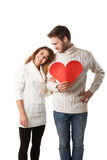 Beautiful young couple holding a red heart. Isolated over white background Stock Photography