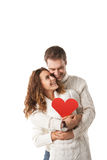 Beautiful young couple holding a red heart. Isolated over white background Royalty Free Stock Image