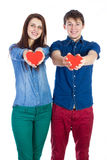 Beautiful young couple holding a small red paper heart in hands Royalty Free Stock Images