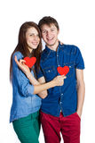 Beautiful young couple holding a small red paper heart in hands Stock Images