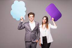 Beautiful young couple is holding speech bubbles, looking at camera and smiling, on gray Royalty Free Stock Photos