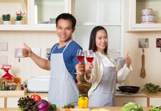 Beautiful young couple is holding wine and thumbs up while cooki. Ng in kitchen at home Royalty Free Stock Photography