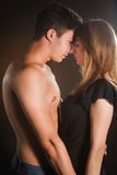 Beautiful young couple hugging and kissing isolated on black background. Stock Photography