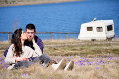 Beautiful young couple  hugging and sitting on a spring meadow with crocuses Royalty Free Stock Photo