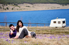 Beautiful young couple hugging and sitting on a spring meadow with crocuses stock images