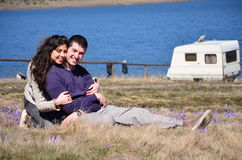 Beautiful young couple  hugging and sitting on a spring meadow with crocuses Royalty Free Stock Photography