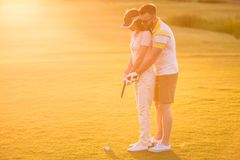 Couple playing golf. Beautiful young couple is hugging and smiling while playing golf Stock Image