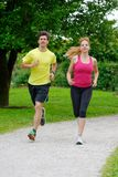 Beautiful young couple jogging in park Royalty Free Stock Photography