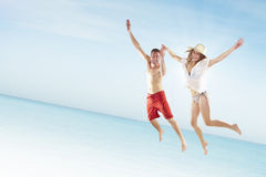 Beautiful young couple jumping on the beach Stock Photos