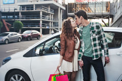 Beautiful young couple kisses near a car, makes a shopping stock photography