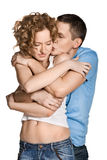 Beautiful young couple kissing. Against white background Stock Photography