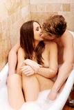 Beautiful young couple kissing in a bath. Stock Images