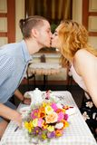 A beautiful young couple is kissing in a cafe. Summer vacation with your beloved Royalty Free Stock Photo