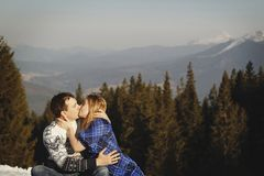 Beautiful couple kissing outdoors over amazingly snowy mountains Stock Images