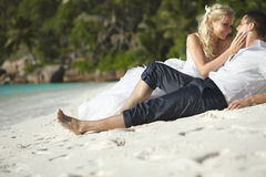 Beautiful young couple kissing on sunset lying on sand, sunset t Stock Photos