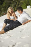 Beautiful young couple kissing on sunset lying on sand, sunset t Stock Photography