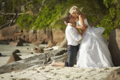 Beautiful young couple kissing on sunset, standing barefoot on b. Beautiful young couple enjoying sunset, walking barefoot on beach and playing with each other royalty free stock images