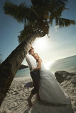Beautiful young couple kissing on sunset, standing barefoot unde Stock Photography